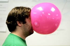 Image of a man being hit in the face with a soft, pink ball